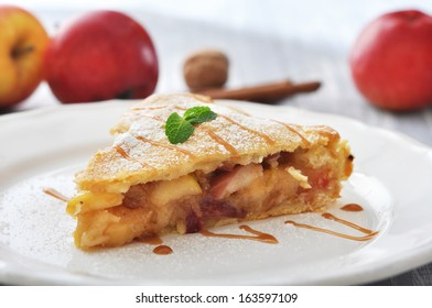 Slice of homemade apple pie with fresh apples on wooden background