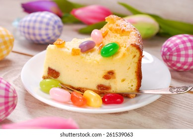 slice of homemade cheesecake with egg shaped candies decoration on easter table