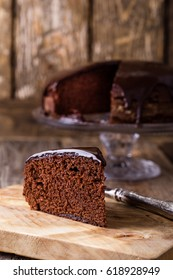 Slice of homemade chocolate cake on wooden cutting board, rustic style