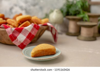 Slice of Homemade Cornbread Isolated on a Small Plate with a Wooden Bowl Full of Homemade Muffins, Slices, and Sticks with Red & White Checked Napkin in the Background
