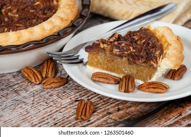 A slice of homemade pecan pie with pecans on rustic wooden table