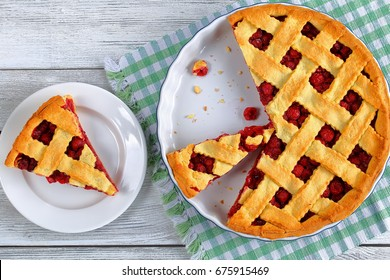 slice of homemade sour cherry pie on plate and whole tart cut in slices in baking dish on napkin on wooden table, classic recipe, view from above