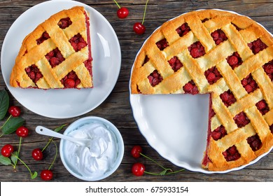 slice of homemade sour cherry pie on plate and whole tart cut in slices in baking dish on dark wooden table with whipped cream in bowl and fresh ripe cherries, classic recipe, view from above