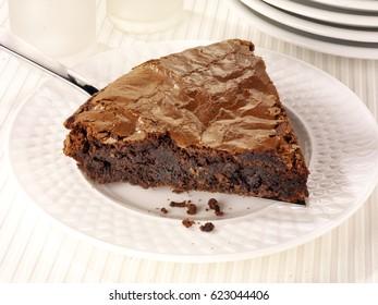 SLICE OF ITALIAN CHOCOLATE CAKE OR TORTA DI CIOCCOLATA ON WHITE PLATE