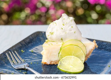 A slice of key lime pie served with whipped cream and lime zest