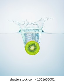 slice of kiwi falls into the water scattering a lot of splashes and drops.