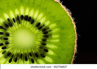 slice of kiwi fruit close-up on black background. horizontal. space for text
