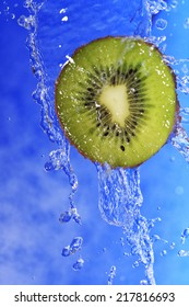 slice of kiwi in the water with bubbles on blue background
