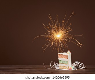 Slice of layered Birthday cake with lit sparkler against a brown background