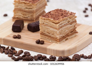 Slice of layered honey cake with coffee beans, candies and black cup, selective focus