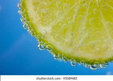 slice of lemon in the blue water with bubbles