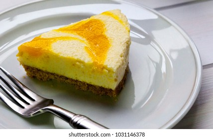 A slice of Lemon Cheese Cake on white dessert plate and folk.