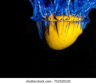 Slice of lemon falling into water, black and blue background