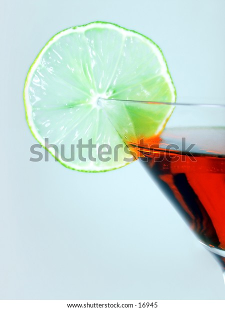 A slice of lemon and partial of a cocktail glass.