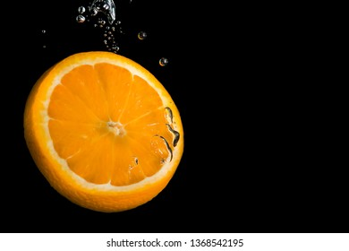 Slice of lemon submerged in water with bubbles on black background and space to add text