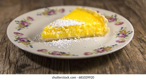 Slice of Lemon Tart isolated on a wood background. Shallow depth of field