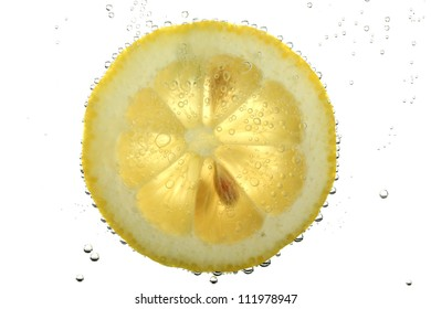 slice of lemon in the water with bubbles, isolated on white