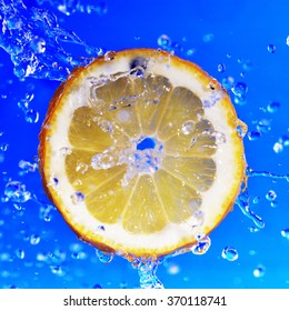 slice of lemon in the water with bubbles on blue background