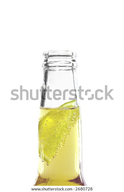 Slice of lime in a freshly opened bottle of beer, isolated on a white background.