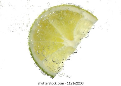 slice of lime in the water with bubbles, isolated on white
