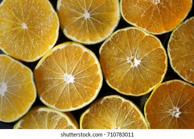 Slice of mandarins on black background . Studio lighting.