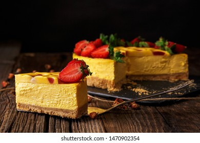 slice of mango cheesecake, with strawberries, on wooden background