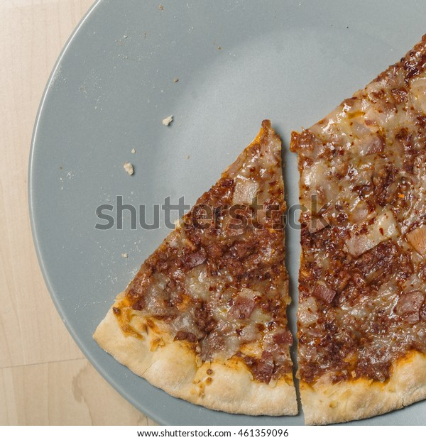 Slice of meat pizza bread close up served on a wooden table