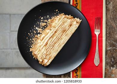 a slice of napoleon cake on a black plate