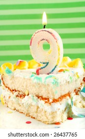 slice of nineth birthday cake with lit candle, confetti, and ribbon (shallow depth of field)