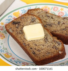 Slice of nut bread with butter on a plate