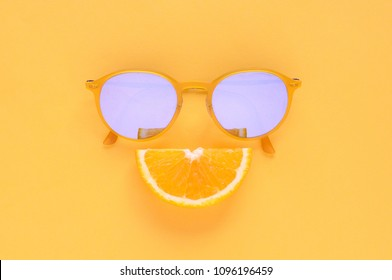 Slice orange fruit and yellow sunglasses isolated on yellow background for summer time with space for text.