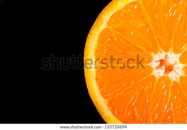 Slice of orange on black background. Selective focus on the slice of orange