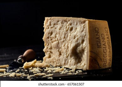 Slice of parmesan cheese with knife over black background