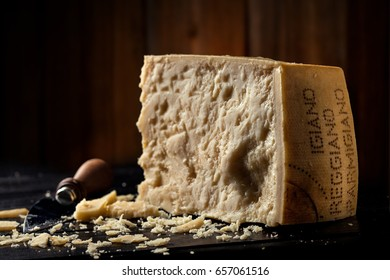 Slice of parmesan cheese with knife over wooden background