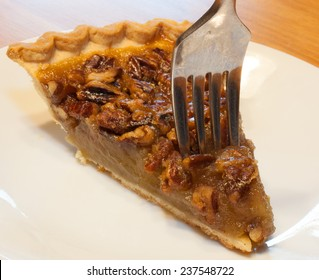 Slice of pecan pie with a fork just going in
