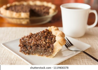 Slice of pecan pie on a white plate with cup of coffee