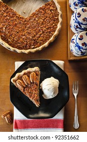 A slice of pecan pie served with vanilla ice cream on a black dish, the whole pie in the background.