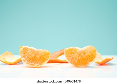 slice and peel of orange on white table against light green background