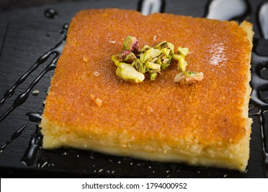 A slice piece of kunafa Arabic sweet pastries dessert on dish with creamy cheese pistachio.