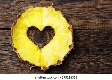 Slice pineapple with a cut in shape of hearts on vintage wooden background