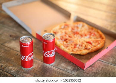 slice pizza in box and can of coca-cola on wood background