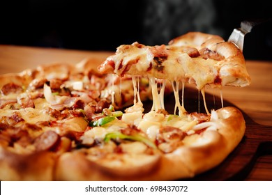 Slice of pizza cheese crust seafood topping sauce. with bell pepper vegetables delicious tasty fast food italian traditional and soft drink carbonated fresh on wooden board table classic and smoke