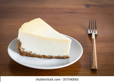 Slice of Plain New York Cheesecake on white plate on wooden background