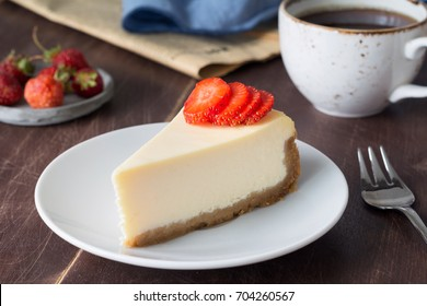 Slice of plain new york cheesecake with fresh strawberries, cup of coffee and newspaper on wooden table. Breakfast, lunch or snack at cafe