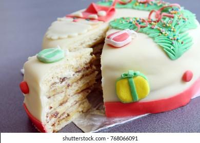 slice, portion of handmade decorated with sugar paste, fondant christmas cake: cut of banana and chocolate cake