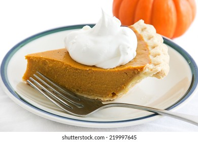 Slice of pumpkin pie garnished with a dollop of whipped cream.