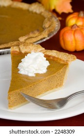 A slice of pumpkin pie on the holiday table. The whole pie is seen in the background.