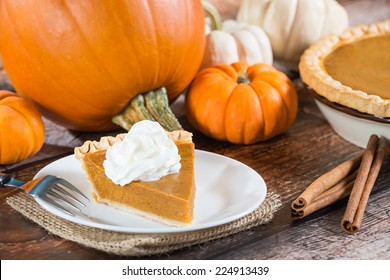 Slice of a pumpkin pie and pumpkins on wooden table