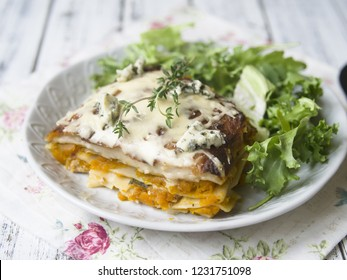 Slice of Pumpkin and Spinach Lasagne with blue cheese and salad on a White Wooden Table. Selective focus, copy space, close up