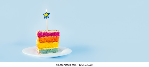 Slice of Rainbow cake with birning candle in the shape of star on white round plate isolated on blue background. Happy bithday, party concept. Wide banner. Selective focus. Copy space